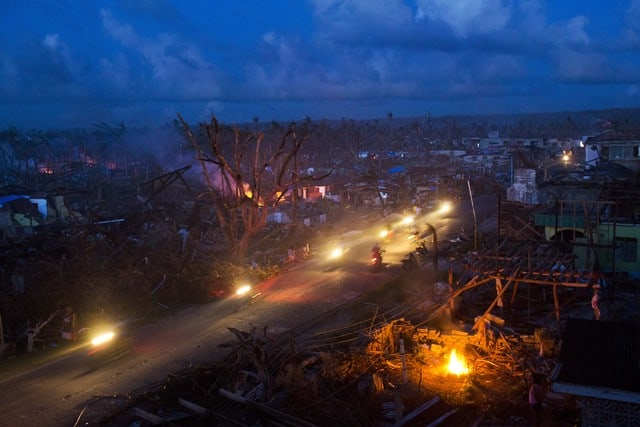 Typhoon Haiyan survivors ride motorbikes through the ruins of the destroyed town of Guiuan, Philippines. (Photo: AP)