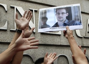 A supporter holds a picture of Edward Snowden, a former NSA employee who leaked top-secret information about U.S. surveillance programs, outside the U.S. Consulate General in Hong Kong on June 13, 2013. (AP Photo/Kin Cheung)