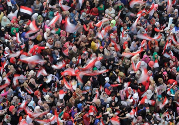 Egyptian women wave flags in support of Egypt's military on the third anniversary of the Tahrir Square uprising in Cairo, Egypt. (AP Photo/Amr Nabil)