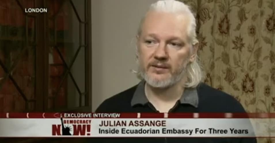 """Julian Assange sits down to talk to """"Democracy Now!"""" host Amy Goodman in this still from the show's video coverage of their interview in London. (Democracy Now!)"""